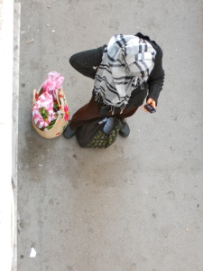 A woman in her headscarf with traditional shopping basic pausing to text from her cell phone